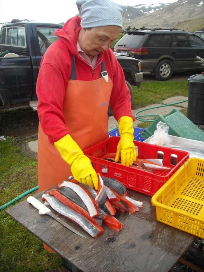 Mom stripping red salmon to hang them in the smoke house.